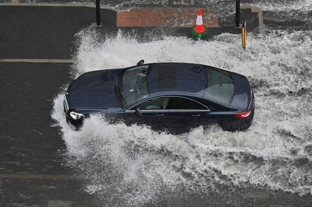 A car drives through deep water on a flooded road in Nine Elms, London on July 25 during heavy rain (Photo: JUSTIN TALLIS via Getty Images)