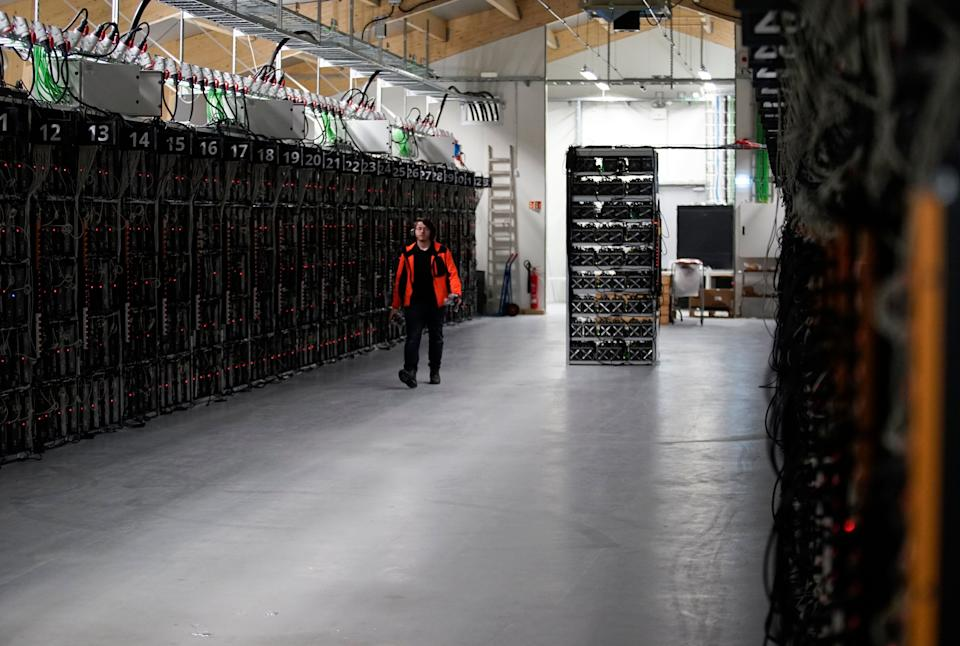 """In this photo taken on Jan. 17, 2018, a worker walks along a row of computer rigs that run around the clock 'mining' bitcoin inside the Genesis Mining cryptocurrency mine in Keflavik, Iceland. Hand in hand with the rise of bitcoin is a soaring cost of """"mining"""" the cryptocurrency. The energy demand has developed because of the soaring cost of producing the cryptocurrency, which requires computers solving math formulas to mine the 4.2 million coins still available. (AP Photos/Egill Bjarnason)"""