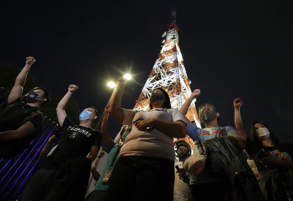 Employees and supporters of ABS-CBN raise their clenched fist as they sing outside their headquarters in Quezon City, Philippines Friday July 10, 2020. Philippine lawmakers voted Friday to reject the license renewal of the country's largest TV network ABS-CBN, shutting down a major news provider that had been repeatedly threatened by the president over its critical coverage. (AP Photo/Aaron Favila)