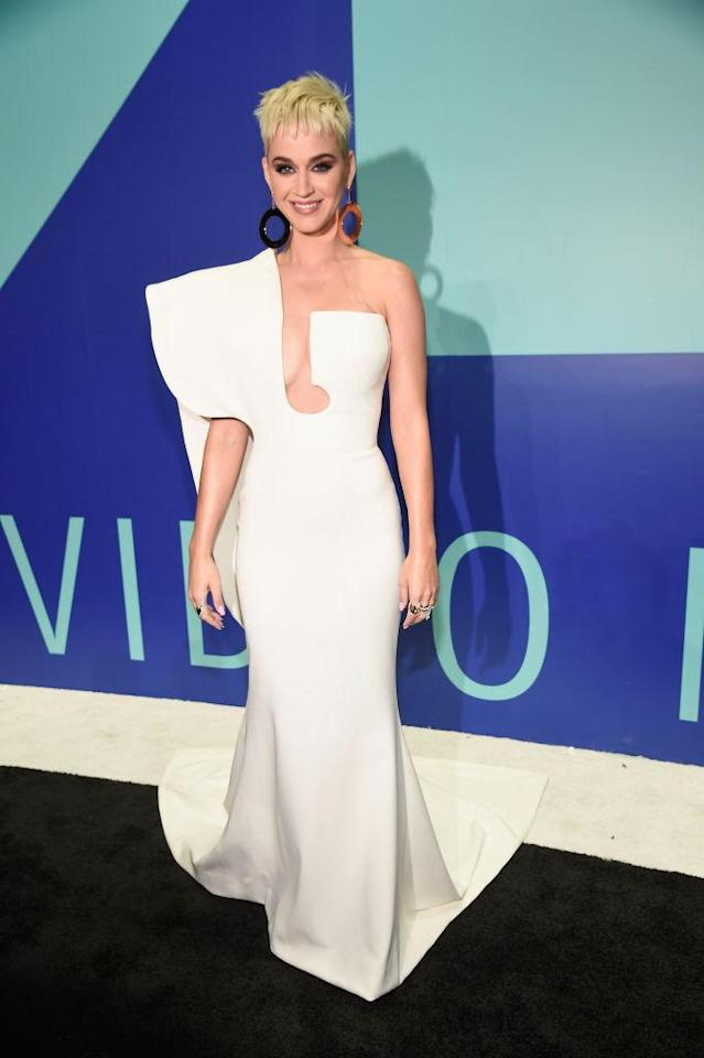 <p>In her first outfit of the night, the 2017 MTV VMAs host opted for understated yet futuristic elegance with a white geometric gown. She paired the piece with oversized circular earrings. (Photo: Getty Images) </p>