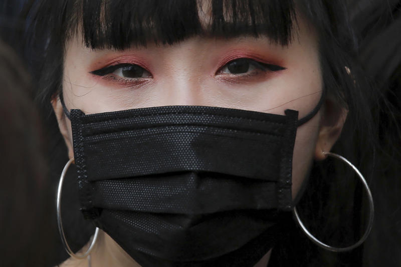 A protester with a mask gathers with others near the Legislative Council as they continuing protest against the unpopular extradition bill in Hong Kong, Monday, June 17, 2019. A member of Hong Kong's Executive Council says the city's leader plans to apologize again over her handling of a highly unpopular extradition bill. (AP Photo/Kin Cheung)