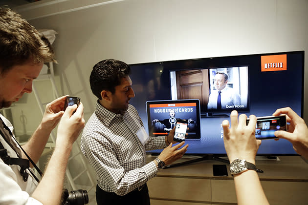 Suveer Kothari, center, displays how the new Chromecast device operates a television with the use of a smartphone. (AP Photo/Marcio Jose Sanchez)