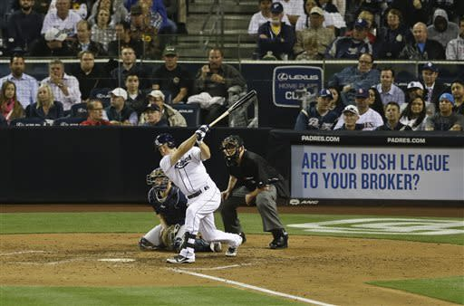 As Milwaukee Brewers catcher Jonathan Lucroy gets on his knees to block a pitch in the dirt as San Diego Padres' Nick Hundley strikes out chasing the pitch in the sixth inning of a baseball game in San Diego, Tuesday, April 23, 2013. The umpire is Gary Darling. (AP photo/Lenny Ignelzi)