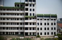 The once-bustling Technical Secondary School in Rudong, Jiangsu province, now a hollow shell looms, over a small group of pupils in the playground (AFP Photo/Johannes Eisele )