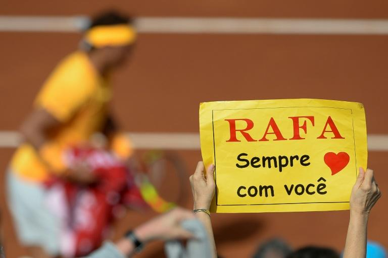 "Fan club: A supporter holds a placard reading ""With you always Rafa"""