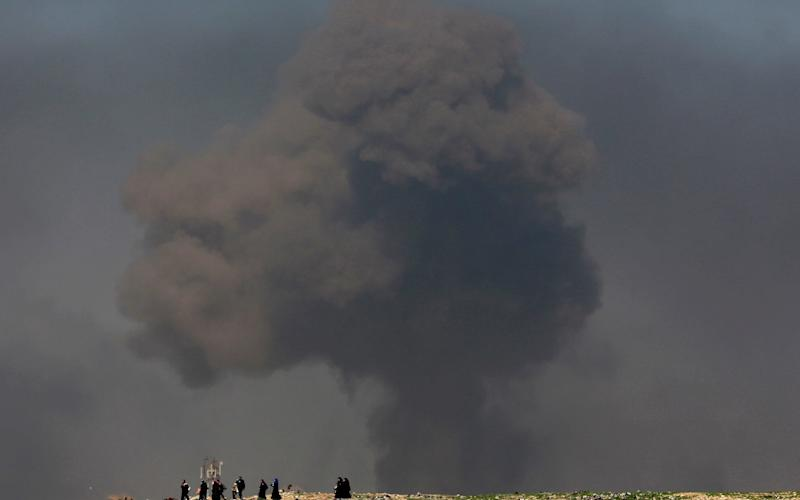 A large cloud of smoke rises during fighting between Iraqi security forces and Islamic State militants as civilians walk toward Iraqi security forces after fleeing their homes on the western side of Mosul, Iraq.