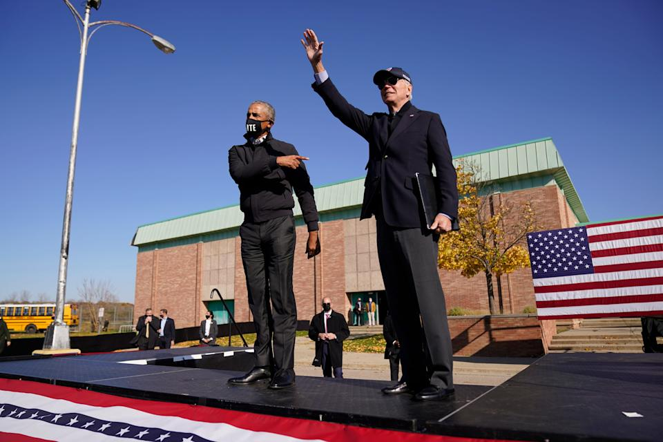 Democratic presidential candidate former Vice President Joe Biden, right, and former President Barack Obama greet each other at a rally at Northwestern High School in Flint, Mich. on Oct. 31, 2020.