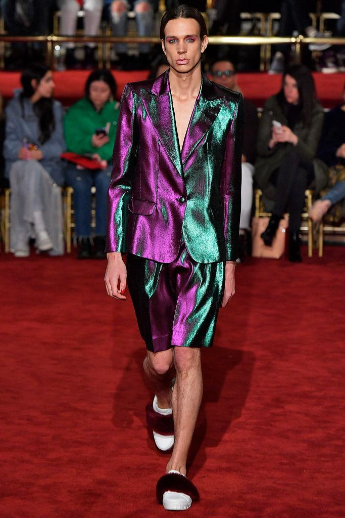 <p>A male model wears an iridescent blazer and short set at the Christian Siriano FW18 show. (Photo: Getty) </p>