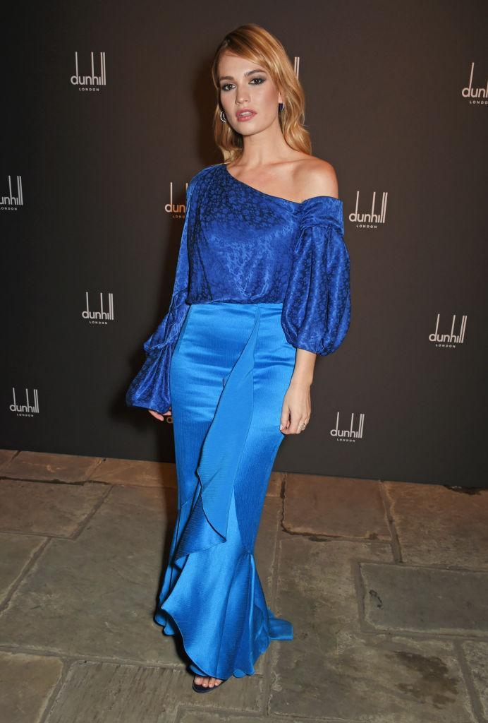 <p>Lily James chose a ruffled silky skirt and one-shoulder blouse for the Dunhill & GQ pre-Bafta filmmakers dinner and party in London. <em>[Photo: Getty]</em> </p>