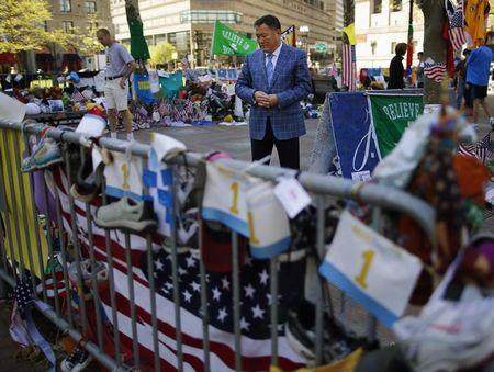 Amir Ismagulov, the father of Azamat Tazhayakov, visits the makeshift memorial for the victims of the Boston Marathon bombings in Boston, Massachusetts May 7, 2013. REUTERS/Brian Snyder/Files