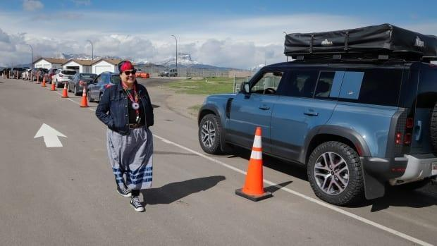 Bonnie Healey, health director for the Blackfoot Confederacy, chats with southern Alberta residents lining up at the border crossing at Carway, Alta., to get shots of a COVID-19 vaccine from the Blackfeet Tribe at a mobile clinic just over the border in Montana on May 18, 2021.  (Jeff McIntosh/Canadian Press - image credit)