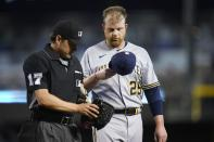 Umpire D.J. Reyburn (17) examines the glove and cap of Milwaukee Brewers starter Brett Anderson, right, as the pitcher leaves a baseball game due to injury during the second inning against the Arizona Diamondbacks, Monday, June 21, 2021, in Phoenix. Beginning Monday, Major League Baseball will enhance its enforcement of rules that prohibit applying foreign substances to baseballs. (AP Photo/Ross D. Franklin)
