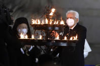 Italian President Sergio Mattarella lights a candle for peace during an inter-religious ceremony for peace in the square outside Rome's City Hall, Tuesday, Oct. 20, 2020 (AP Photo/Gregorio Borgia)