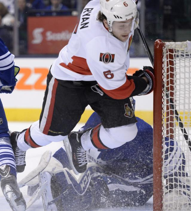 Ottawa Senators' Cody Ceci crashes into Toronto Maple Leafs goalie Jonathan Bernier during first period of an NHL hockey game in Toronto, Saturday, Feb. 1, 2014. (AP Photo/The Canadian Press, Frank Gunn)