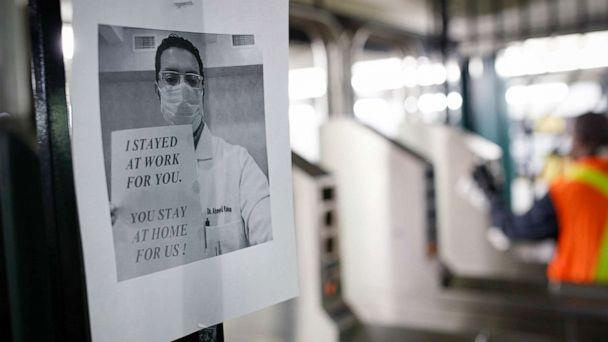 PHOTO: A flier urging customers to remain home hangs at a turnstile as an MTA employee sanitizes surfaces at a subway station with bleach solutions due to COVID-19 concerns, Friday, March 20, 2020, in New York. (John Minchillo/AP)