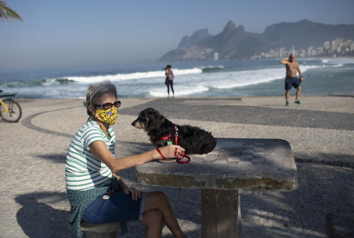 Lucia and her dog Jujuba sit at Arpoador beach, amid the new coronavirus pandemic in Rio de Janeiro, Brazil, Tuesday, June 2, 2020. Rio, the city with the second-most cases after Sao Paulo, is beginning to gradually relax restrictions on Tuesday, only allowing people to exercise on the beachfront sidewalk and practice individual activities in the sea. No one is allowed on the sand. (AP Photo/Silvia Izquierdo)