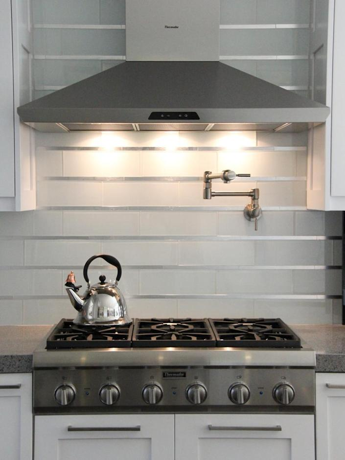 """<p>Stainless steel inserts combine with white glass subway tiles for an almost futuristic vibe in this ultra-modern kitchen. Smart lighting and sleek appliances further the room's high-tech design. <i>Design by Principle Design & Construction. </i><b>RELATED: <a href=""""http://www.hgtv.com/design/rooms/kitchens/5-stainless-steel-kitchen-backsplashes-pictures?oc=PTNR-YahooRealEstate-HGTV-subway_tile_twists"""" rel=""""nofollow noopener"""" target=""""_blank"""" data-ylk=""""slk:20 Stylish Stainless Steel Kitchen Backsplashes"""" class=""""link rapid-noclick-resp"""">20 Stylish Stainless Steel Kitchen Backsplashes</a></b></p>"""