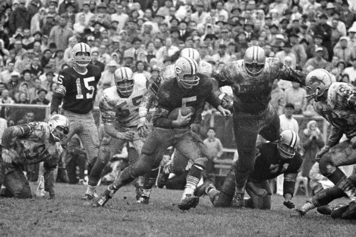 FILE - In this Oct. 7, 1962, file photo, Green Bay Packers halfback Paul Hornung (5) carries the Detroit Lions, including Roger Brown (76, to the right of Hornung), during the second half of an NFL football game in Green Bay, Wis. To the left of Hornung are Lions' Wayne Walker (55) and Packers quarterback Bart Starr (15). Brown, a College Football Hall of Famer and six-time Pro Bowl selection with the Lions and the Los Angeles Rams, has died. He was 84. The Lions and College Football Hall of Fame announced his death Friday, Sept. 17, 2021. The Lions said a member of Brown's family confirmed the death. No cause was given. (AP Photo, File)