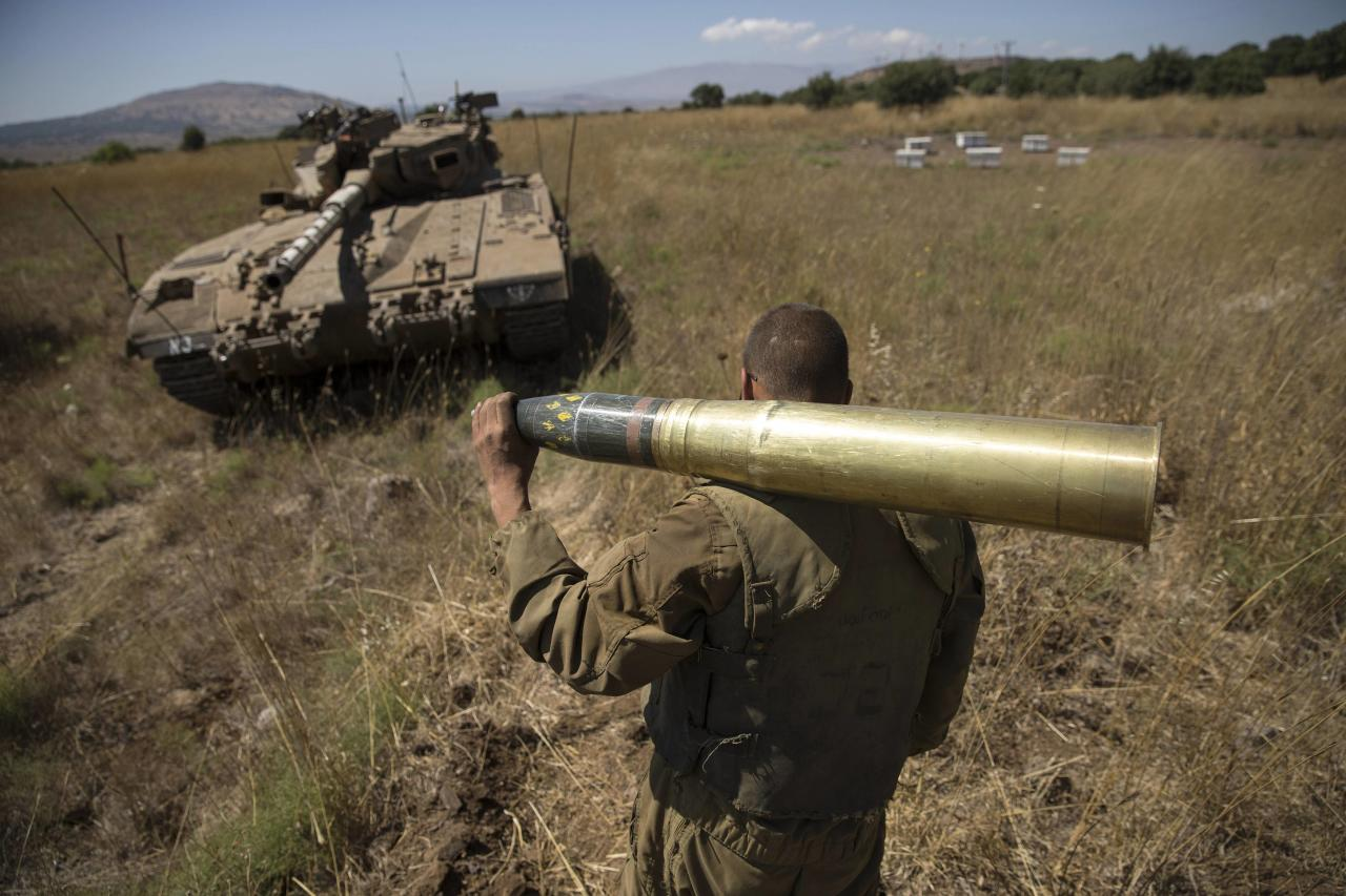 An Israeli soldier carries a tank shell near Alonei Habashan on the Israeli occupied Golan Heights, close to the ceasefire line between Israel and Syria June 22, 2014. An attack from inside Syria on Sunday killed a 13-year-old Israeli boy on the occupied Golan Heights, the first fatality on Israel's side of the frontier since the Syrian civil war began, relatives and the military said. 