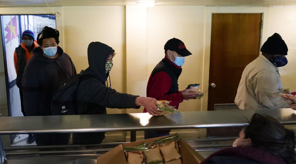 People seeking shelter from sup-freezing temperatures receive a meal at a make-shift warming shelter at Travis Park Methodist Church, Tuesday, Feb. 16, 2021, in San Antonio. (AP Photo/Eric Gay)