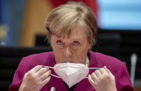 German Chancellor Angela Merkel takes off her mask at the beginning of the Federal Cabinet meeting at the Chancellery in Berlin, Germany, Wednesday, March 3, 2021. (Michael Kappeler/Pool via AP)
