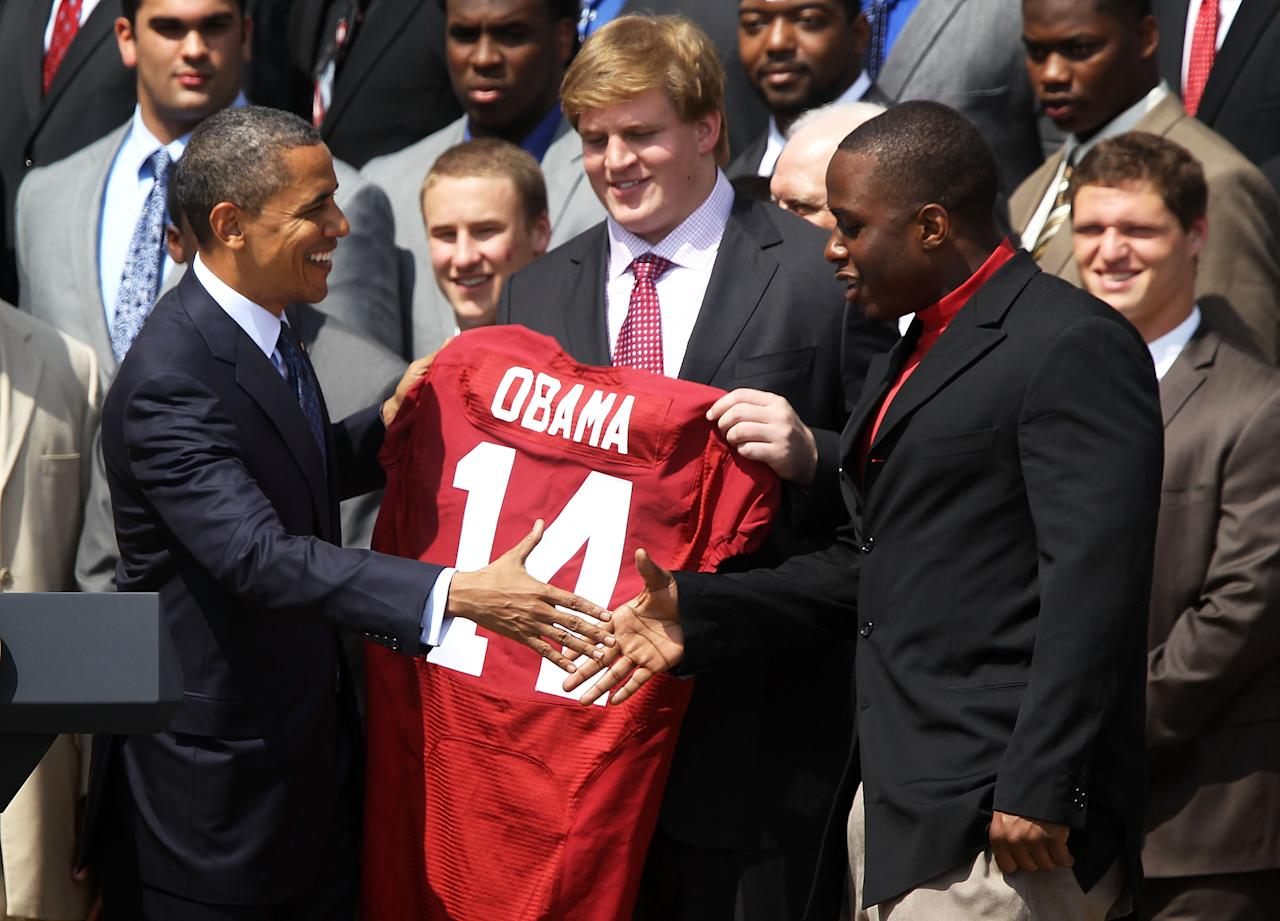 WASHINGTON, DC - APRIL 19:  U.S. President Barack Obama (L) shakes hands with defensive lineman Damion Square (R) as offensive lineman Barrett Jones (2nd R) of the Alabama Crimson Tide looks on after Obama was presented with a jersey of the University of Alabama Crimson Tide during a South Lawn event at the White House April 19, 2012 in Washington, DC. Obama hosted the BCS national champion to honor their win over the Louisiana State University Tigers.  (Photo by Alex Wong/Getty Images)