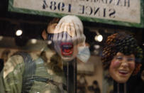 A young man looks at carnival masks reflected in the window of a shop in Venice, Italy, Saturday, Jan. 30, 2021. Last year, with fear over the new coronavirus mounting, authorities abruptly shut down Venice Carnival on its third day, just before Italy became the first country in the West facing a outbreak. (AP Photo/Antonio Calanni)