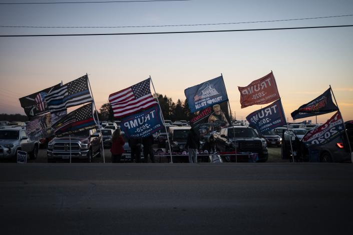 People selling Trump souvenirs fly flags at a parking lot near the venue of his rally, Monday, Nov. 2, 2020, in Kenosha, Wis. Trump has made Wisconsin a focus of his final push, including a stop planned Monday night in Kenosha, while repeatedly refusing to say whether he would agree to a peaceful transfer of power if he loses. (AP Photo/Wong Maye-E)