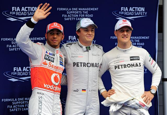 Mercedes-AMG driver Nico Rosberg of Germany (C), McLaren-Mercedes driver Lewis Hamilton of Britain (L) and Mercedes-AMG driver Michael Schumacher of Germany (R) celebrate after the qualifying session of Formula One's Chinese Grand Prix at the Shanghai International Circuit on April 14, 2012. AFP PHOTO / Mark RALSTON (Photo credit should read MARK RALSTON/AFP/Getty Images)