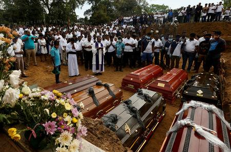 FILE PHOTO: People participate in a mass funeral, of the seven victims belonging to one family, in Negombo, three days after a string of suicide bomb attacks on churches and luxury hotels across the island on Easter Sunday, in Sri Lanka April 24, 2019. REUTERS/Thomas Peter/File Photo
