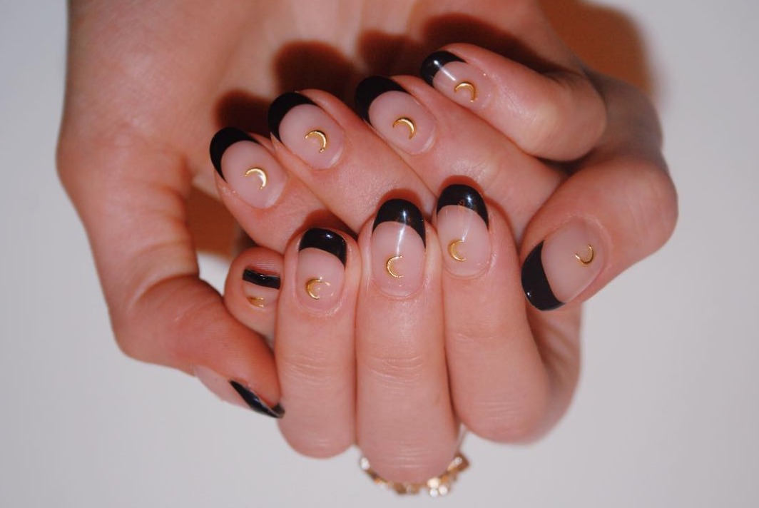 """If you haven't heard, the <a href=""""https://www.glamour.com/story/french-manicure-ideas?mbid=synd_yahoo_rss"""">French mani</a> is making a comeback. Give it a witchy update with black tips and moon decals."""