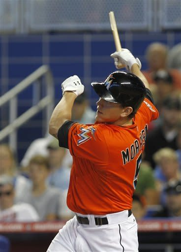 Miami Marlin' Logan Morrison follows through on a broken-bat single against the Chicago Cubs in the first inning of a baseball game in Miami, Thursday, April 19, 2012. Emilio Bonifacio scored on the base hit. (AP Photo/Alan Diaz)