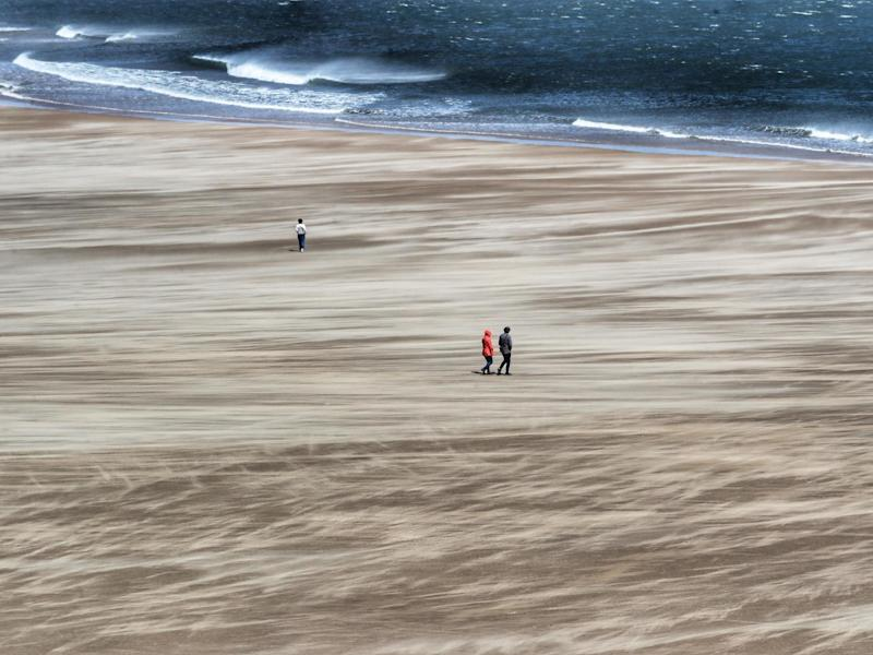 Strong winds whip up the sand as people walk along Tynemouth beach on the north east coast: PA