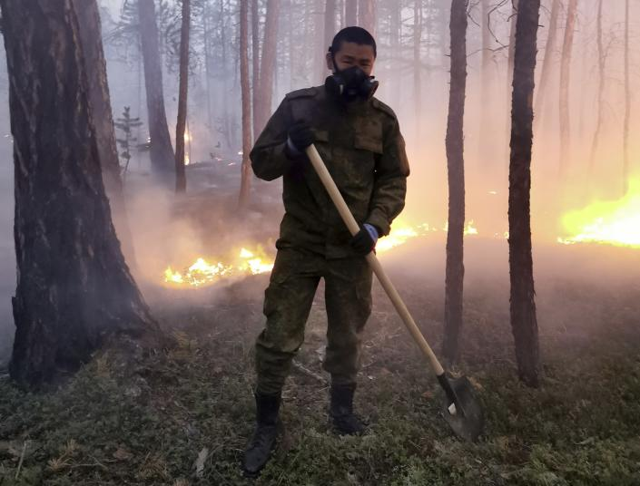 Ivan Nikiforov, member of volunteers crew pose for a photo as he monitors a backfire they lit to stop the fire from spreading at Gorny Ulus area west of Yakutsk, Russia, Saturday, July 17, 2021. As the smoke intensified, Ivan Nikiforov took a leave from his office job in the city — not to escape the bad air but to head into the fires as a volunteer. The volunteers rely on their own money or funds from nongovernmental groups. The hardest hit area is the Sakha Republic, also known as Yakutia, in the far northeast of Russia, about 5,000 kilometers (3,200 miles) from Moscow. (AP Photo/Albert Nogovitsin)