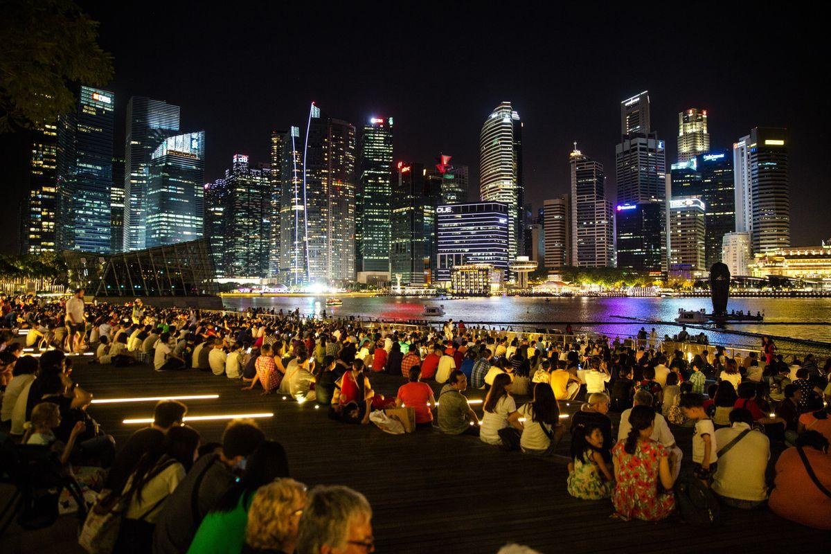 Tourists and visitors sit along the bay of the Marina Bay Sands as buildings in the central business district stand illuminated at night in Singapore, on Sunday, June 4, 2017. Hunger for Singapore land is adding to signs the citys housing market is making a comeback after three years of declining prices. With new home sales surging after an easing of property restrictions in March, developers are becoming more aggressive in bidding at land auctions.