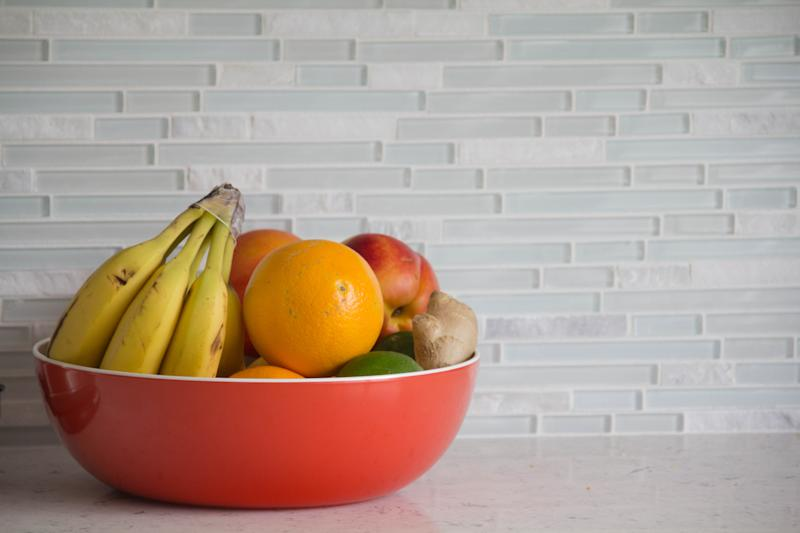 Red bowl with fresh fruit on grey granite kitchen counter with glass tile backsplash.