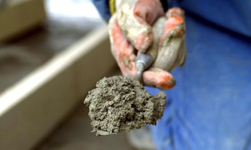 Hand holding a trowel loaded with cement