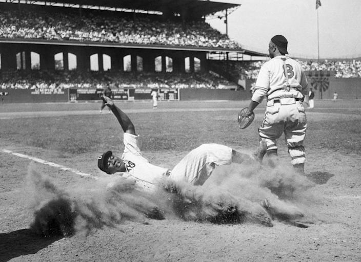 """<span class=""""caption"""">Josh Gibson slides into home during the 1944 Negro Leagues All-Star Game.</span> <span class=""""attribution""""><a class=""""link rapid-noclick-resp"""" href=""""https://www.gettyimages.com/detail/news-photo/josh-gibson-of-the-east-team-creates-a-cloud-of-dust-as-he-news-photo/514700378?adppopup=true"""" rel=""""nofollow noopener"""" target=""""_blank"""" data-ylk=""""slk:Bettmann/Getty Images"""">Bettmann/Getty Images</a></span>"""