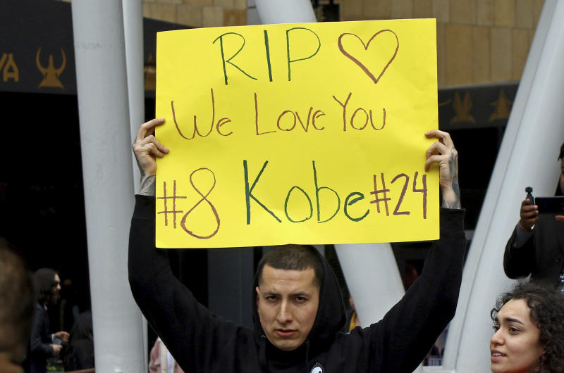 A man holds a sign memorializing Kobe Bryant at the LALive area across from Staples Center, home of the Los Angeles Lakers, after word of the Lakers star's death in a helicopter crash in downtown Los Angeles Sunday, Jan. 26, 2020. (AP Photo/Matt Hartman)