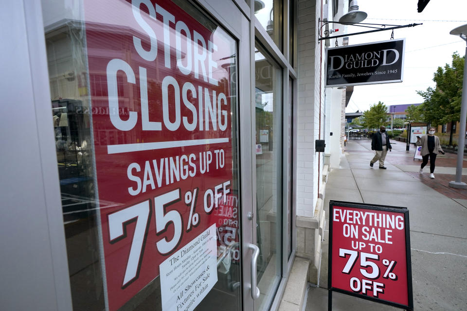 In this Sept. 2, 2020 photo, aassers-by walk past a business storefront with store closing and sale signs in Dedham, Mass. The coronavirus and the drastic measures put in place by government officials to try to control its spread had a severe toll on many small businesses in the U.S. (AP Photo/Steven Senne)