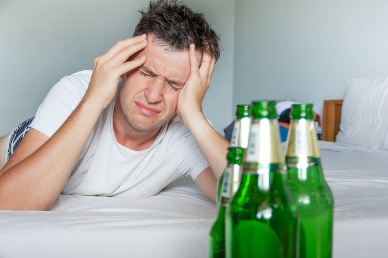 Man lies in bed, clutching his head, with beer bottles in view.