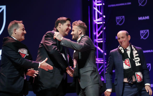 David Beckham, second from right, hugs investor Marcelo Claure, second from left, at an event where it was announced that Major League Soccer is bringing an expansion team to Miami, Monday, Jan. 29, 2018, in Miami. At left is investor Jorge Mas, and at right is MLS Commissioner Don Garber. (AP Photo/Lynne Sladky)