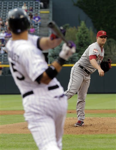 CORRECTS TO THURSDAY NOT WEDNESDAY - Houston Astros starting pitcher Bud Norris, right, follows through on a throw to Colorado Rockies' Carlos Gonzalez as Gonzalez hits a three-run home run in the first inning of a baseball game on Thursday, May 31, 2012, in Denver. (AP Photo/Joe Mahoney)