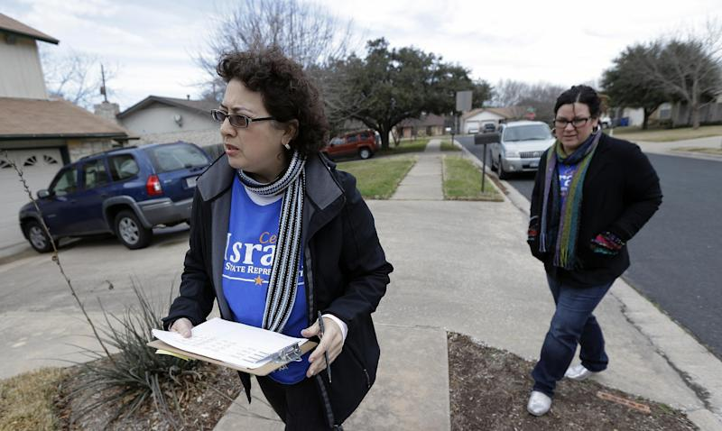 FILE - In this Jan. 28, 2014 file photo, Texas House of Representatives hopeful Celia Israel, left, walks door-to-door asking for votes, in Austin, Texas. A year ago this week Democrats created an organization to revitalize and rebuild a moribund party with the longest losing streak in the country. And while there are few competitive races in the Democratic primaries, one key measure of the party's health is whether a charismatic candidate like Wendy Davis and a voter-mobilizing group like Battleground Texas has sparked the enthusiasm necessary to boost turnout. (AP Photo/Eric Gay, File)