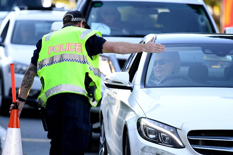 A police officer directs a car for further inspection at a check point on the Queensland-New South Wales border in Coolangatta.
