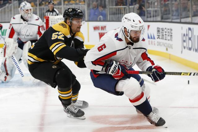 Boston Bruins' Sean Kuraly (52) defends against Washington Capitals' Michal Kempny (6) during the first period of an NHL hockey game in Boston, Saturday, Nov. 16, 2019. (AP Photo/Michael Dwyer)