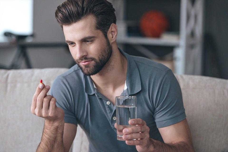 man holding a glass of water and looking at a pill in his hand while sitting on the couch