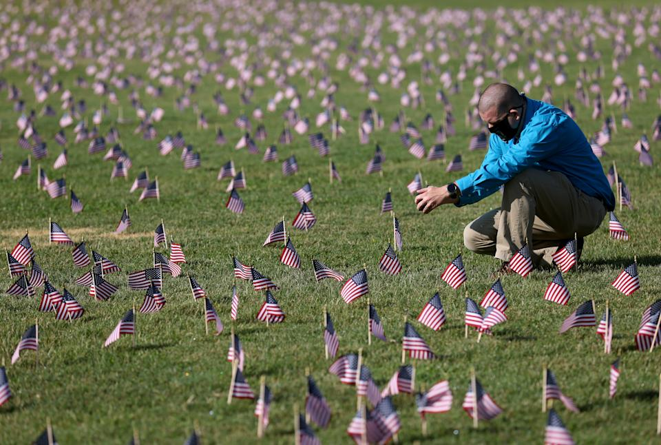 Chris Duncan, whose mother died from Covid on her birthday, photographs a Covid Memorial Project in September after the US hits more than 200,000 virus deaths. Source: Getty