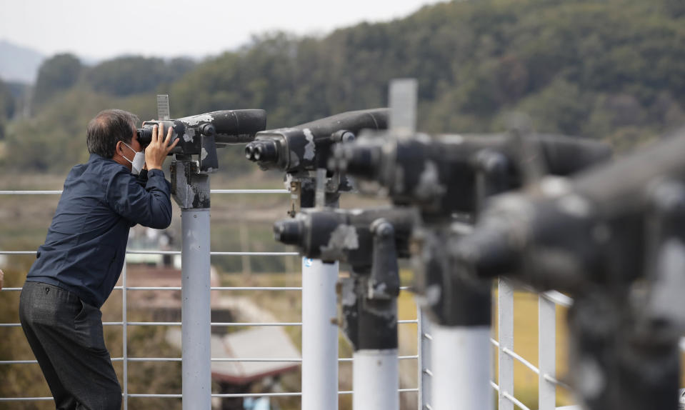 "A man wearing a face mask uses binoculars to view from the Imjingak Pavilion in Paju, South Korea, Sunday, Oct. 11, 2020. North Korean leader Kim Jong Un warned that his country would ""fully mobilize"" its nuclear force if threatened as he took center stage at a military parade that unveiled what appeared to be a new intercontinental ballistic missile and other weapons Saturday. (AP Photo/Lee Jin-man)"