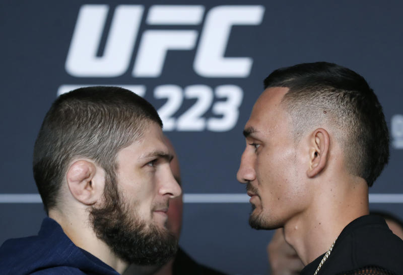 Khabib Nurmagomedov, left, poses for photographers with UFC featherweight champion Max Holloway, Thursday, April 5, 2018, during UFC223's media day at the Barclays Center in New York, ahead of their lightweight championship bout Saturday, April 7th, at the Brooklyn arena. (AP Photo/Kathy Willens)